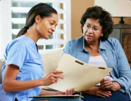 Nurse discussing records with senior patient