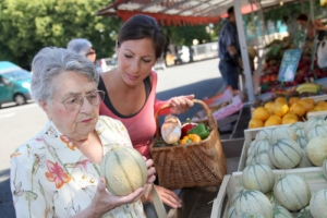 caregiver assisting an old woman in a grocery